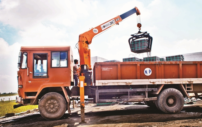 The Chowgule 360 Degree Truck Mounted Crane being used at the storage facility of a brick and block manufacturing organization. The crane is coupled with a mechanical grappler for quickly and securely handle brick bundles.