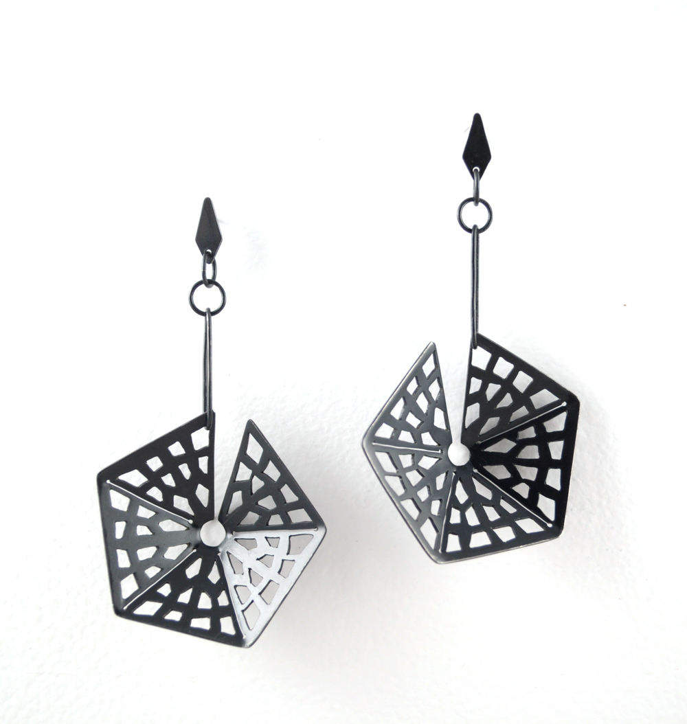 E3 Tolbert, Jess geo print steel hexagon hanging on bar with small leaf attached at top.jpg