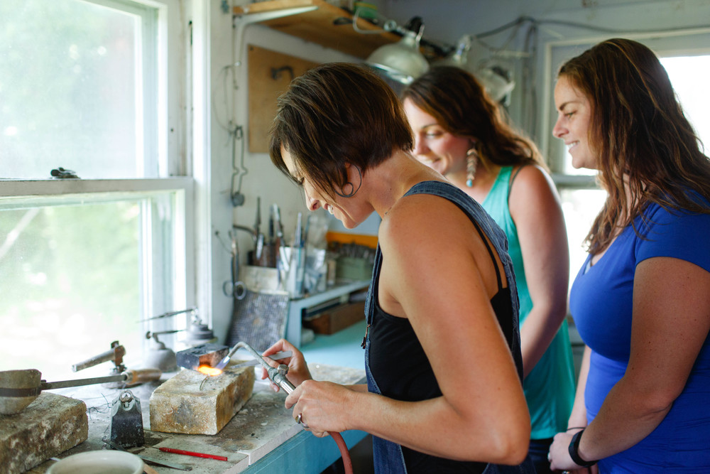 Heidi demonstrates soldering to her students.