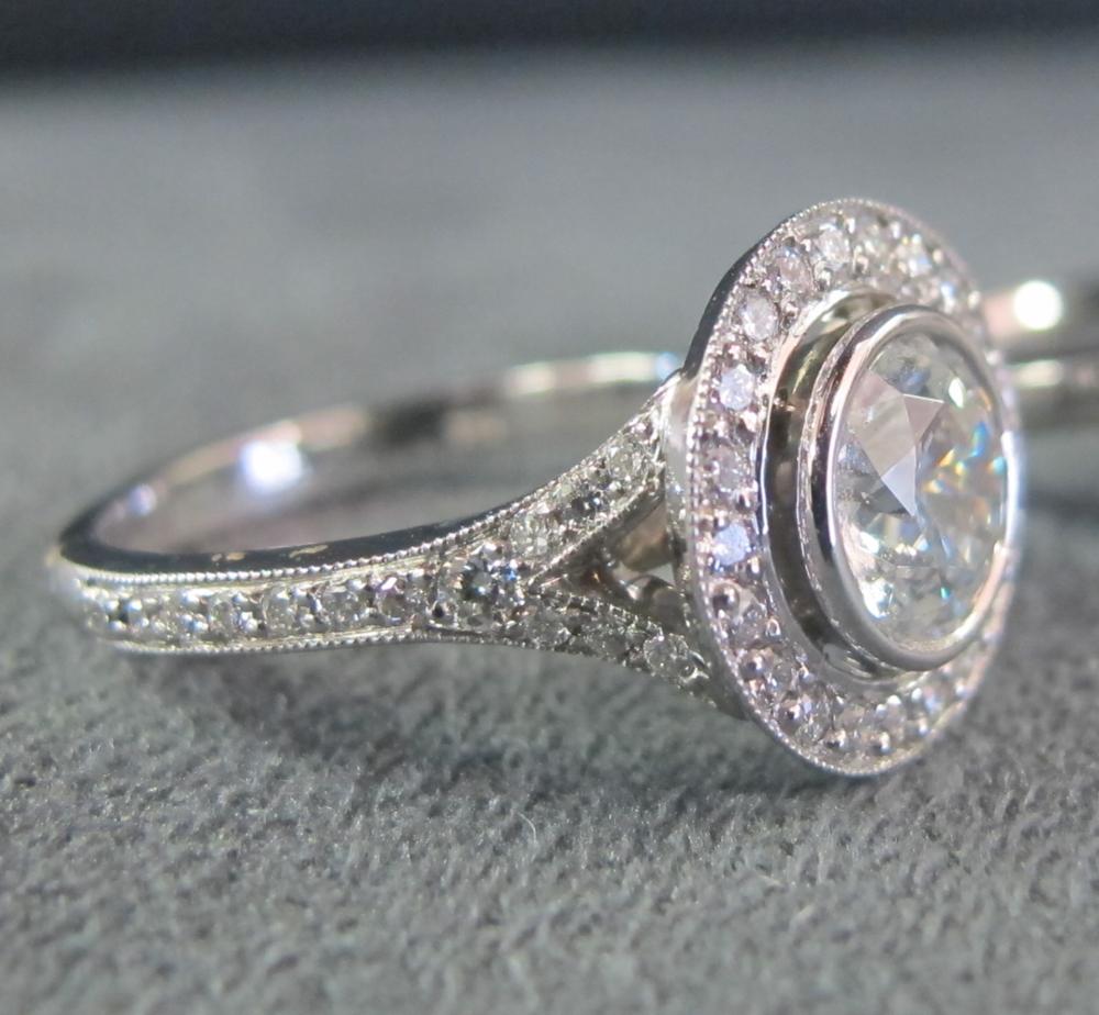 Platinum Vintage tTyle engagement ring with round brilliant centre diamond bezel set, split shank diamond band and halo of diamonds.