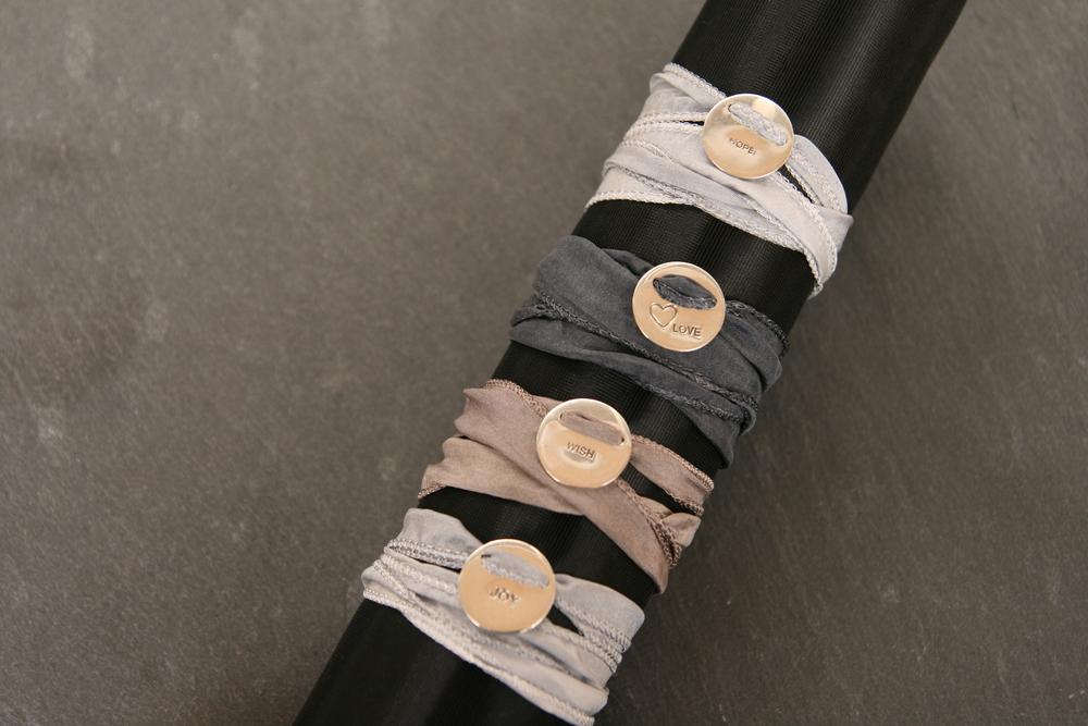 OPE|LOVE|WISH|JOY   Handgefertigte polierte Silberanhänger mit eingearbeitetem Text auf breitem Seidenband. Anhänger: ca. 15mm Durchmesser, Seidenband: 20mm breit; Bänder in den Farben hellgrau, taupe und dunkelgrau erhältlich, Text: LOVE, JOY, HOPE, WISH (auf Nachfrage sind auch andere Farben der Bänder erhältlich!)    BESTELLEN >>   35€