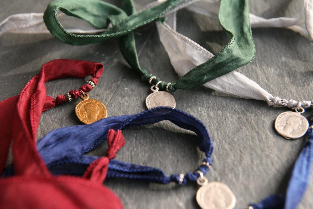 FARBENFROH  2cm breites Seidenband mit gold- oder silberfarbigem Anhänger zum Verknoten. Medaillon: ca. 1,5cm; Band in den Farben hellgrau, weinrot, dunkelblau und dunkelgrün erhältlich.   BESTELLEN >>   28€