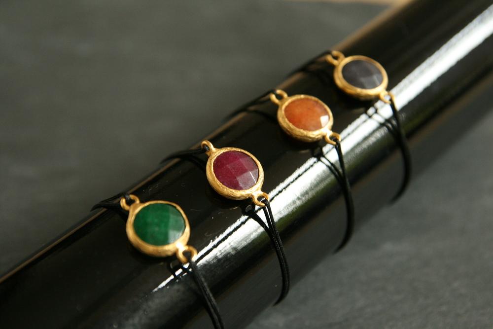 ARMBAND JADE  Farbige Jade-Anhänger in vergoldeter Fassung. Erhältlich in den Farben dunkelgrau, rot, orange, dunkelgrün; Durchmesser der Steine ca. 14mm.  28€   BESTELLEN >>
