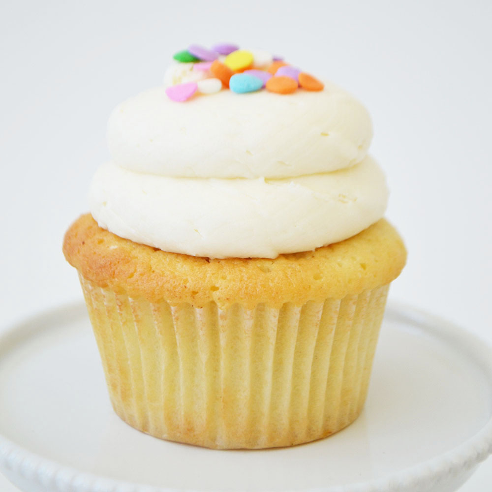 Vanilla Cupcake - Dense vanilla cake topped with vanilla buttercream and confetti sprinkles.
