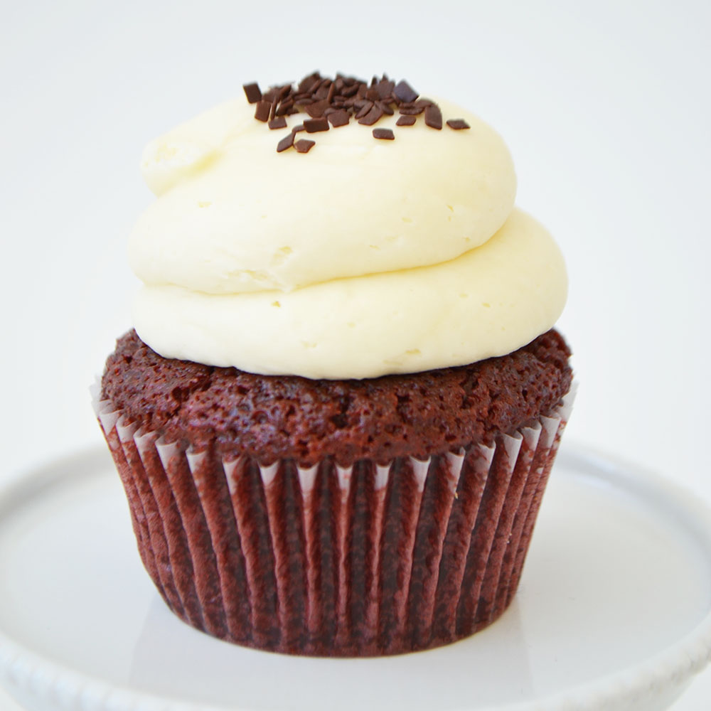 Red Velvet Cupcake  - Moist red velvet cake topped with cream cheese icing and chocolate sprinkles.