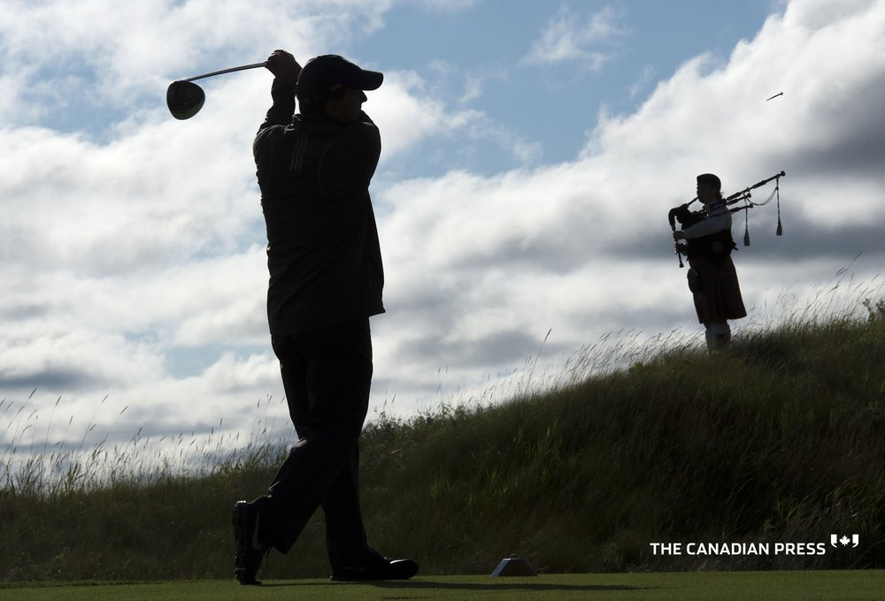 Doug Carrick took the ceremonial opening shot as the bagpipes played.  Photo courtesy of Frank Gunn, Canadian Press.