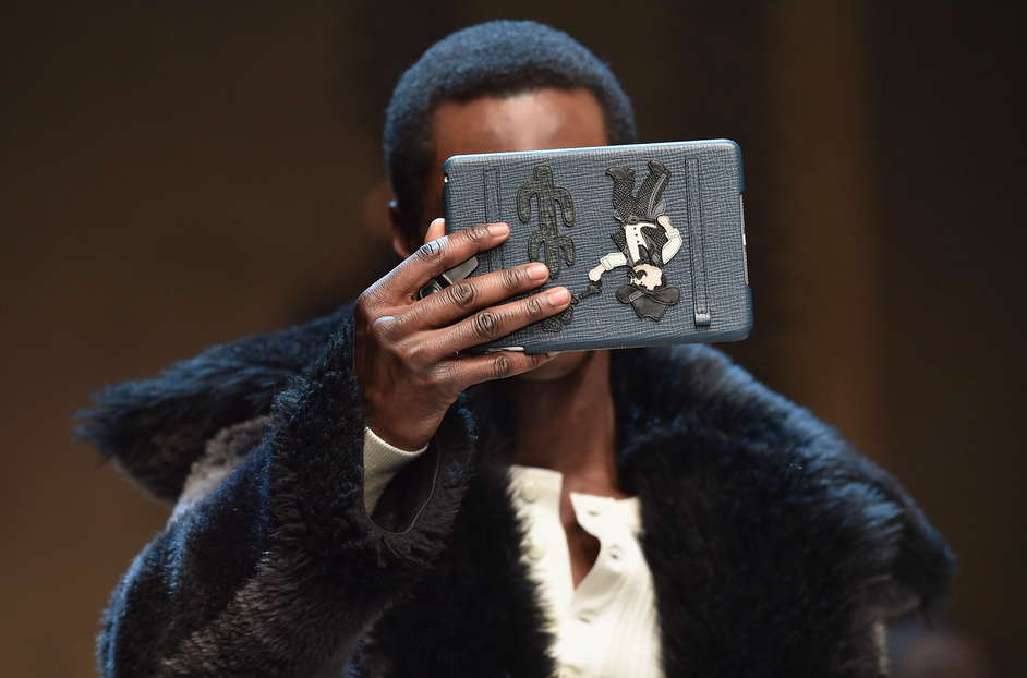 A model walks the runway, iPad in hand, at Dolce & Gabbana's fall show. Photographer: Jacopo Raule/Getty Images
