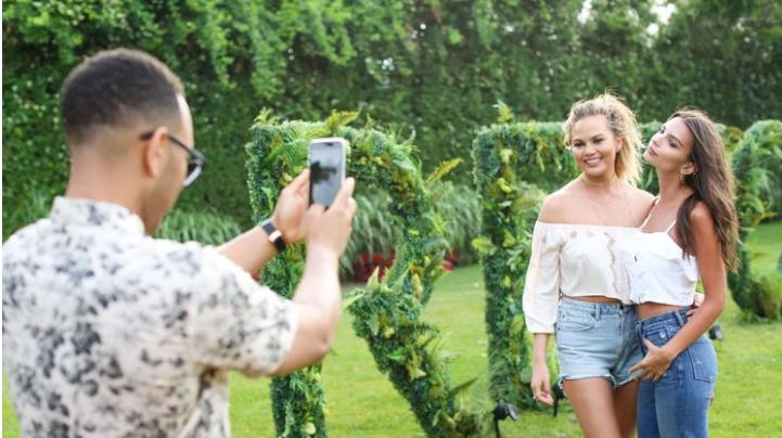 With an iPhone in hand, John Legend takes a photo of wife Chrissy Teigen and Emily Ratajkowski. (David X Prutting / BFA / REX / Shutterstock)