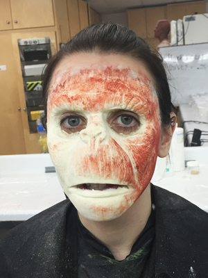 After gluing the prosthetic to my partner's face, red makeup is applied to emulate the appearance of blood vessels under the skin.