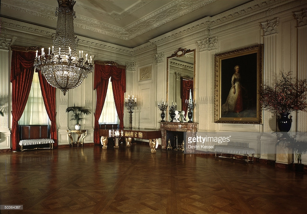 This photo shows the East Room as it appeared under President and Mrs. Franklin Roosevelt,  ca.  1938, with the new, and, on the whole, less delicately treated, Steinway art case grand. According to a 1937 special in  The New York Times , the earlier gold drapery was chosen by Mrs. Theodore Roosevelt and was a deviation from the original 1902 design, with which, according to the article, the red damask pictured here was 'in harmony'. This has not been verified. It is useful to note, however, that while the red does not necessarily offend, the square shape, plain mahogany veneer, and large, detached eagle legs of the 1938 piano are made rather clumsy by the comparative grace and splendor of the room. (Photo by Dmitri Kessel, contrib., The LIFE Image Collection, Getty Images.)