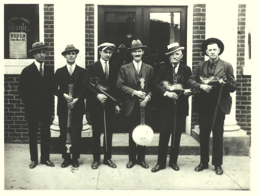 """Stuart, second from right, at the Fiddlers' Convention in Mountain City, Tennessee,May 1925. Also pictured, L to R: Al Hopkins, Joe Hopkins, Alonzo Elvis Alderman, John Rector (the """"Hill Billies""""), and Fiddlin' John Carson. Southern Folklife Collection, Wilson Library Special Collections, UNC."""
