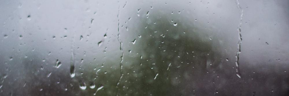 Raindrops drizzle down century old windows.