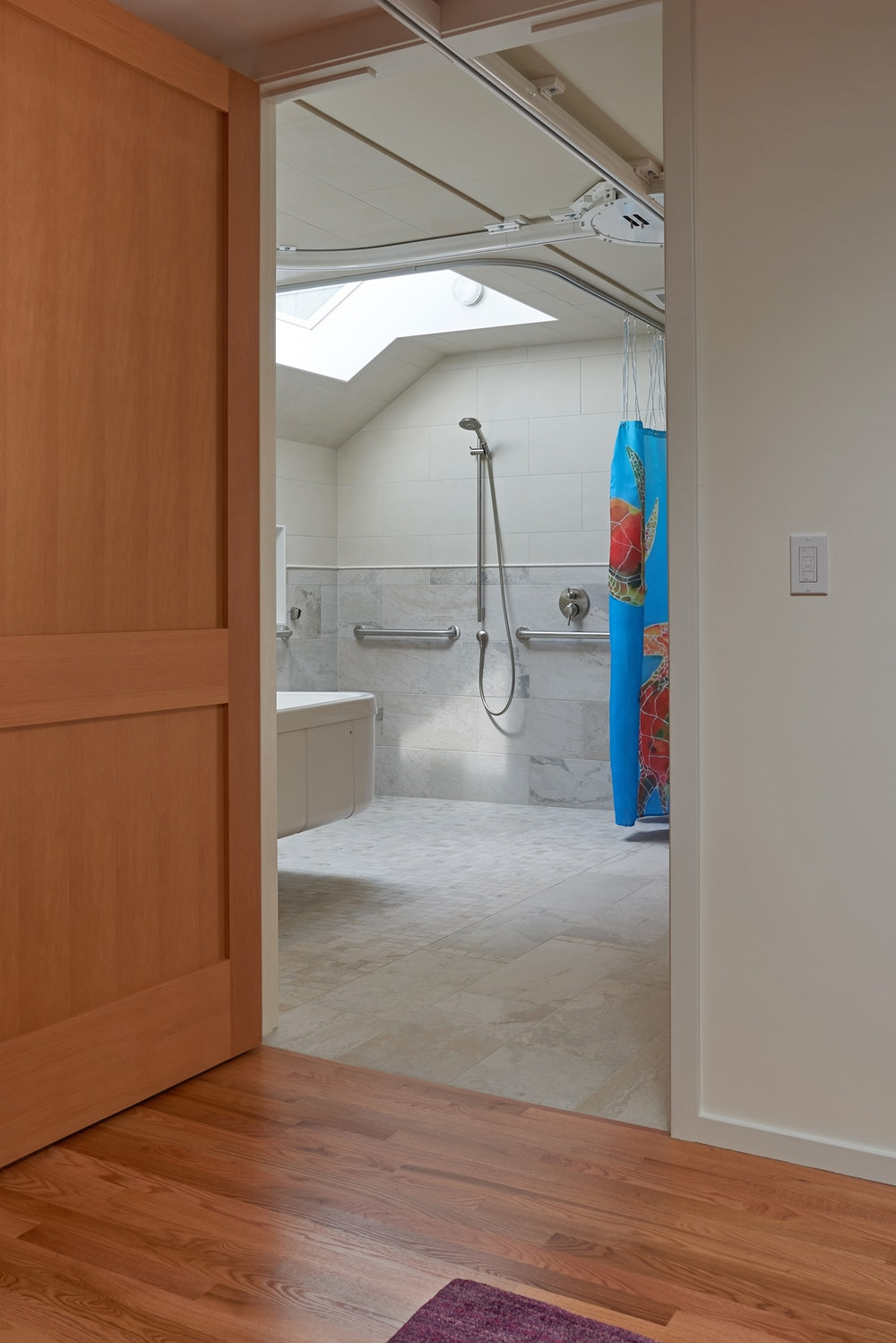 The bathroom features an adjustable-height tub and open shower area washed in natural light.