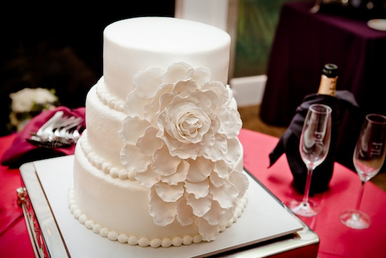 white wedding cake with large flower | photo by www.chiphotographyofcharleston.com