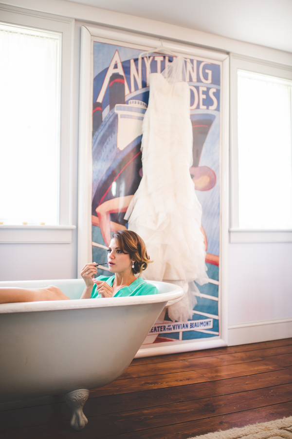 great shot of bride applying makeup in a clawfoot tub | photo by Jessica Oh Photography