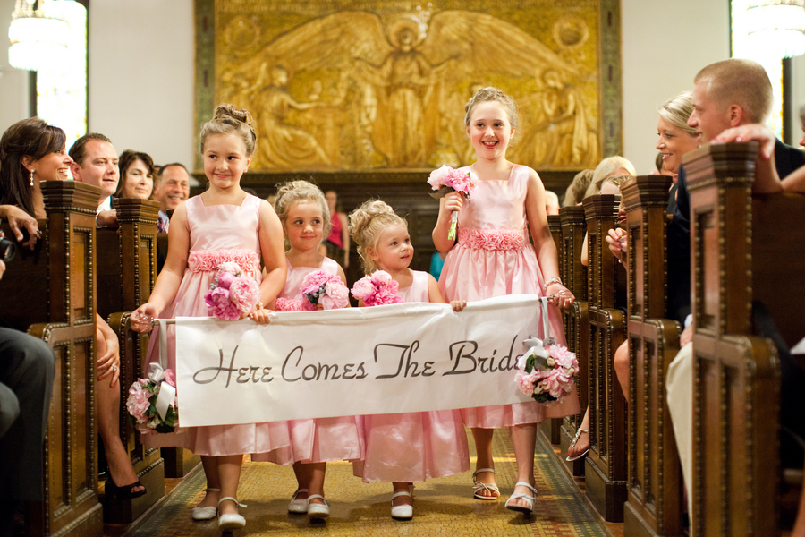 "LOVE this - the flower girls carrying a banner that reads ""Here Comes the Bride"" 