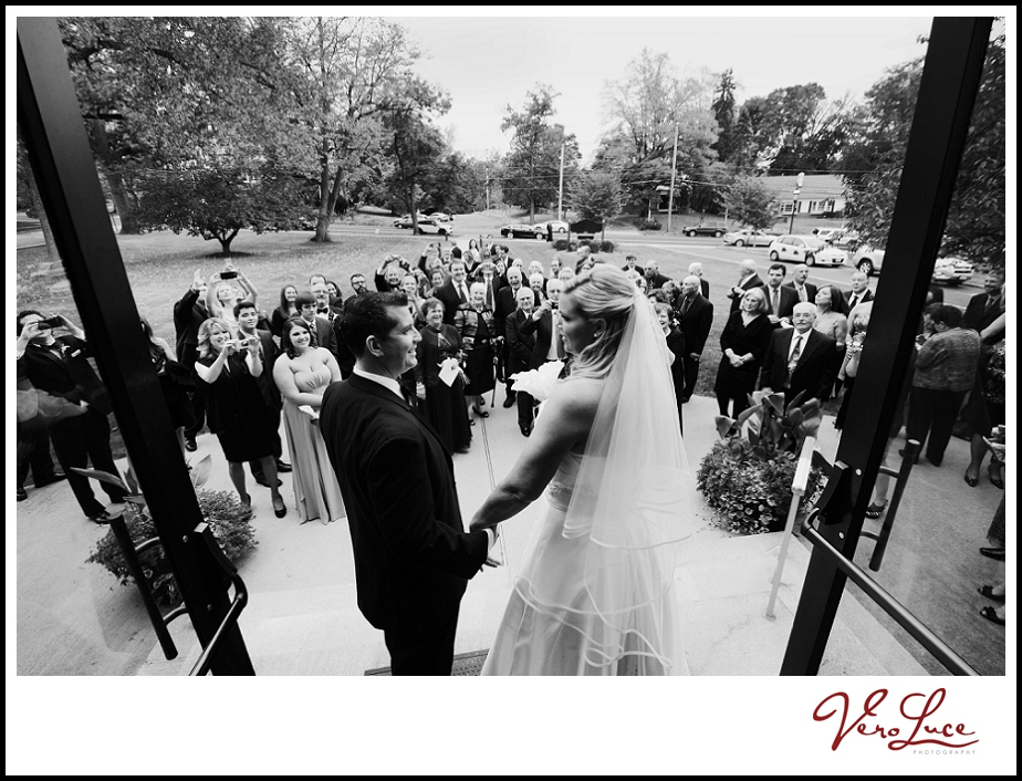 Beautiful aerial photo of the wedding guests watching the bride and groom exit the doors | by VeroLuce Photography www.verolucephotography.com