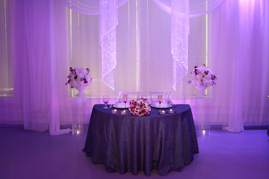 sweetheart table with purple uplighting | photo by Tab McCausland Photography