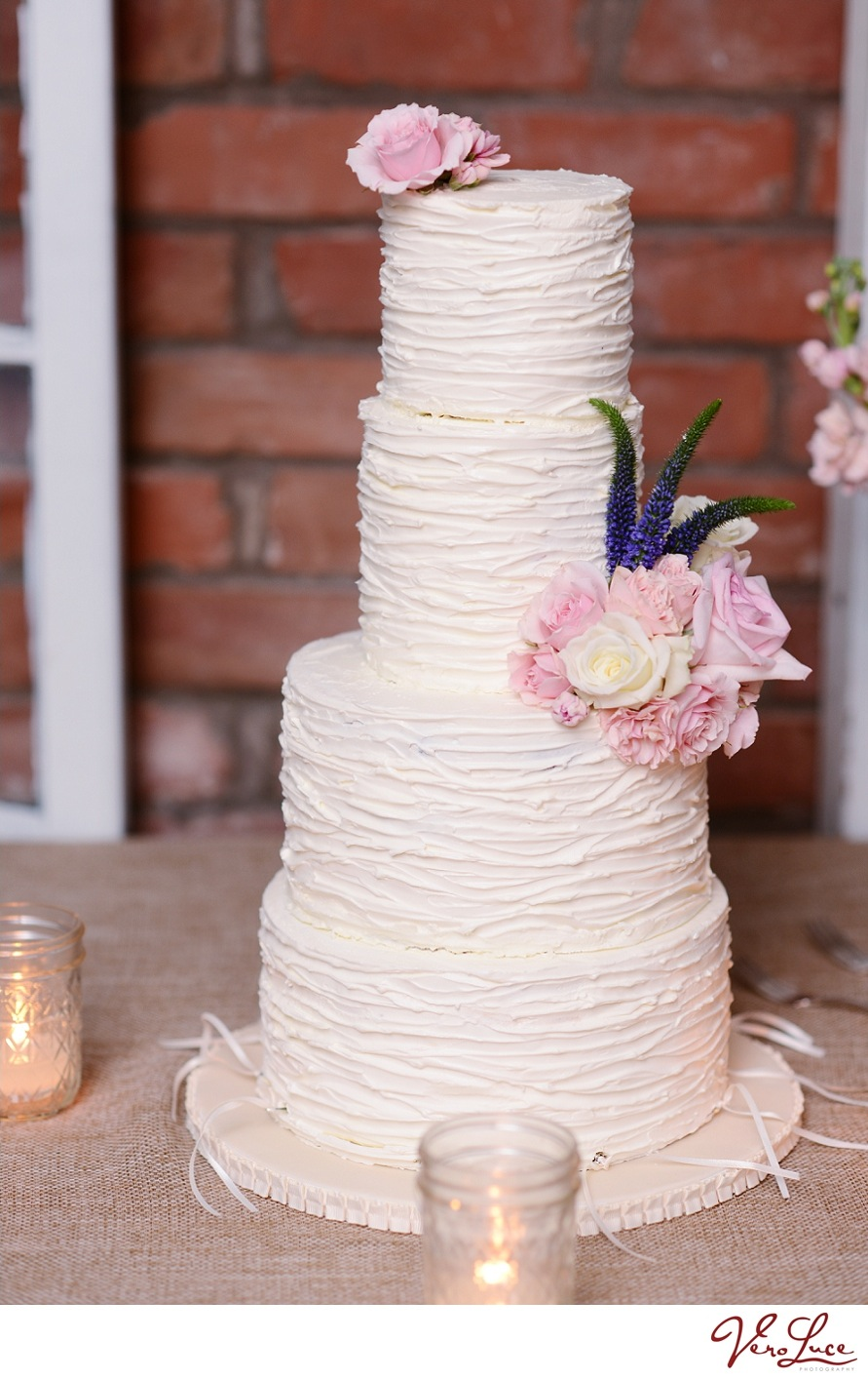 White wedding cake that matches the ruching on the brides dress and her bouquet | photo by VeroLuce Photography
