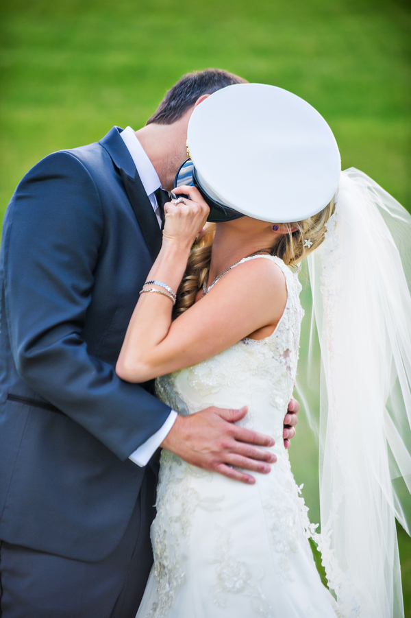Bride Stealing a Kiss Behind the Hat | photo by Ross Costanza Photography | as seen on www.brendasweddingblog.com