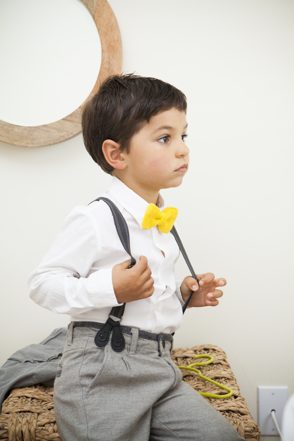 DIY Barn Wedding - ring bearer in suspenders with yellow bow tie / photo by Town Country Studios / as seen on www.BrendasWeddingBlog.com