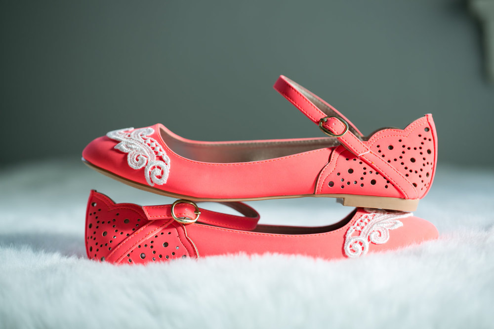 Neon coral colored faux suede ballet flat embellished with an ivory lace applique