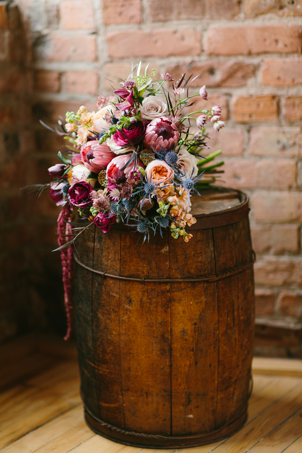 Lush Wedding Bouquet in deep tones of burgundy with accents of pink, peach, champagne, blue + lavender / from Wallflower Designs / photo by Maggie Fortson Photography
