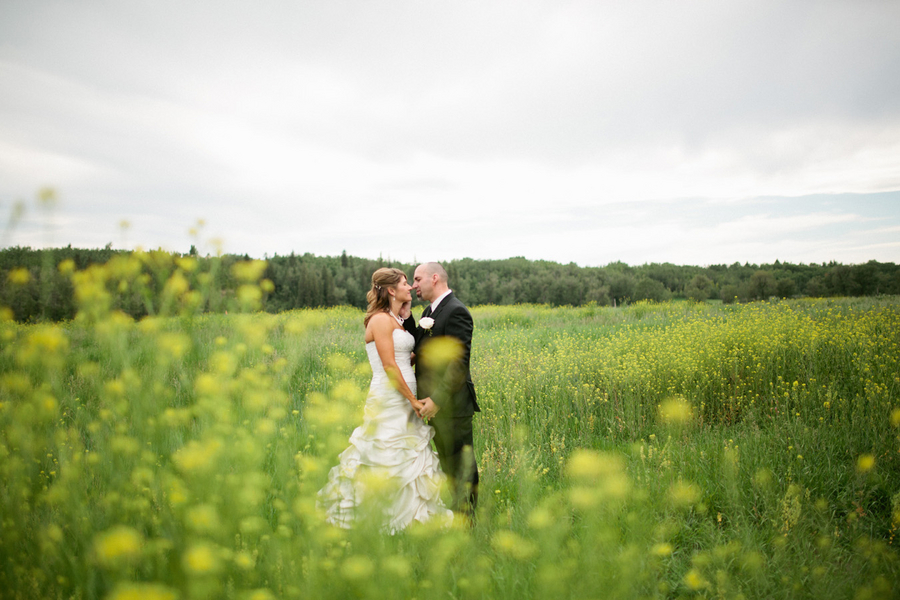 Gorgeous Intimate Moment Captured by Loree Photography of the Canadian Bride and Groom in a Field of flowers