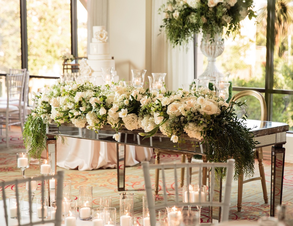 Wedding Reception Idea : go fancy with the head table and a lush floral arrangement + candles / from Anoush Banquet Halls & Catering in CA