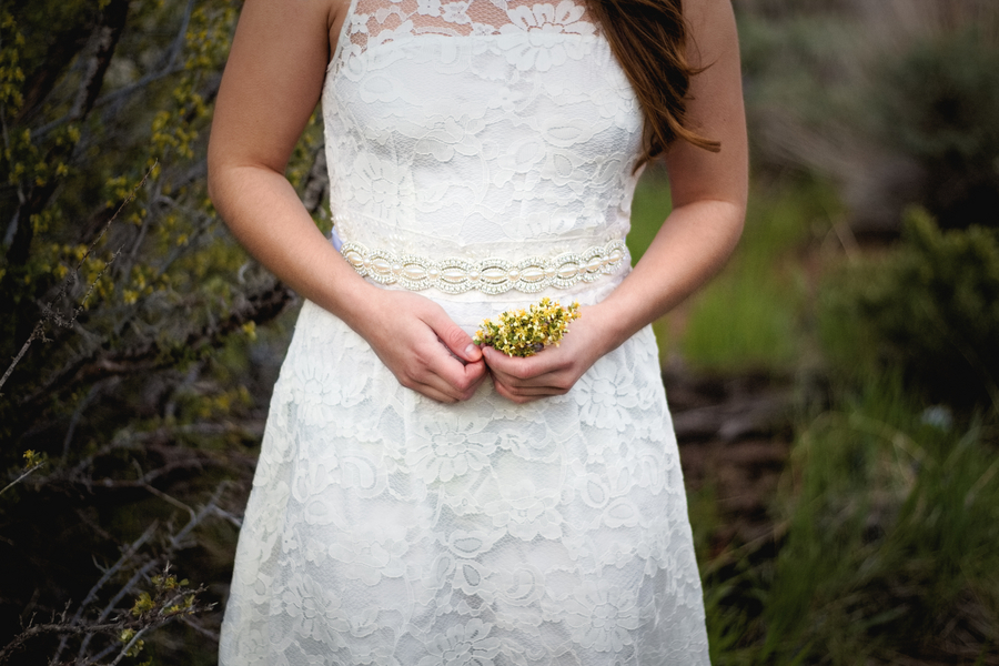 A simple sprig of wildflowers is all you need with your wedding gown has intricate lace all over / photo by Autumn Noel Photography