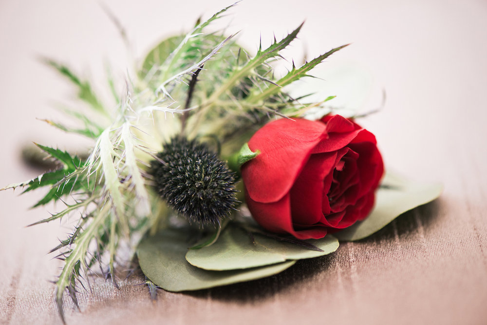 Gorgeous Red Rose andThistle Boutonniere — luxurious and romantic vintage wedding inspiration — photo by Marianne Blackham Photography — as seen on www.BrendasWeddingBlog.com