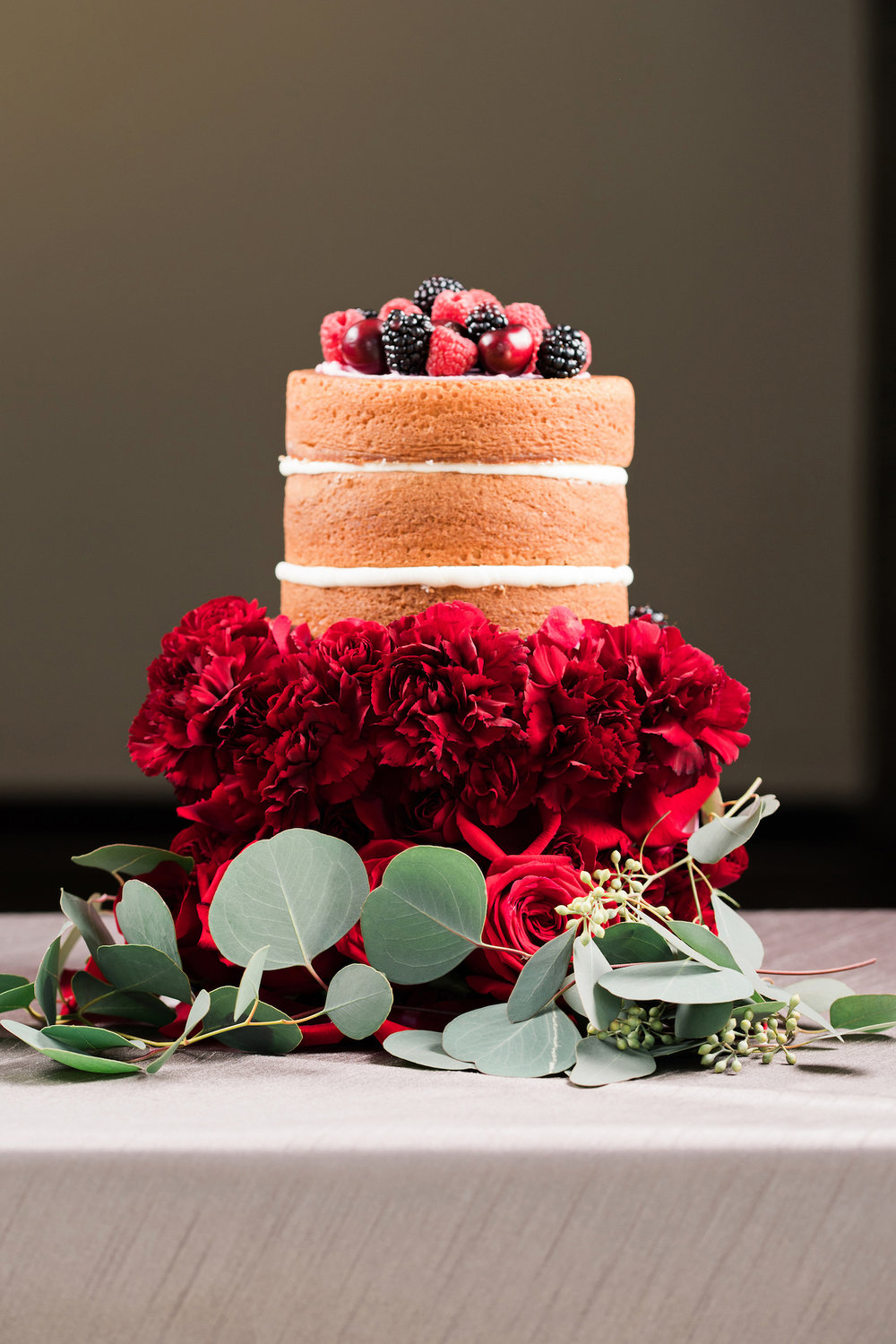 Naked Wedding Cake surrounded by red carnations and green eucalyptus leaves, topped with berries — luxurious and romantic vintage wedding inspiration — photo by Marianne Blackham Photography — as seen on www.BrendasWeddingBlog.com