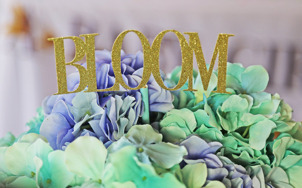 Gold Glittered Cake Toppers that are re-purposed as floral centerpiece sticks — Click to see 37 Creative DIY Wedding Ideas for Spring — as seen on www.BrendasWeddingBlog.com