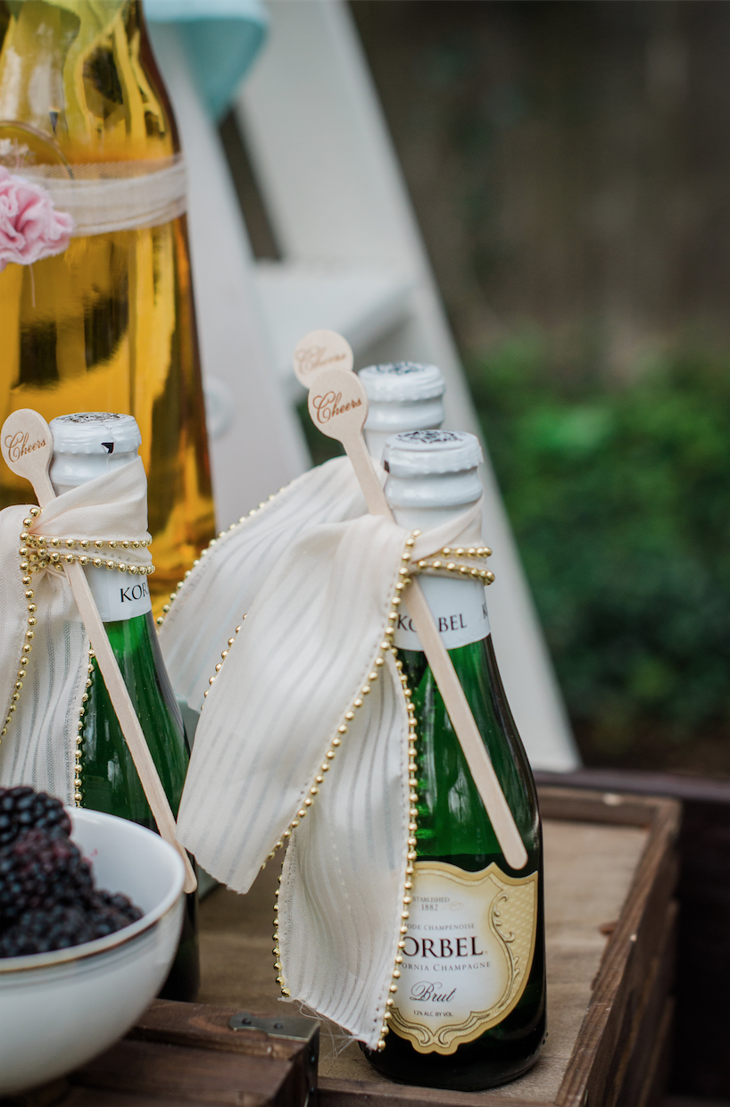 Mini Champagne Bottles presented with fancy ribbon and a cheers drink stirrer attached — Click to see 8 DIY Wedding Ideas for a Springtime Bridal Shower Brunch — Part of the 37 Creative DIY Wedding Ideas for Spring as seen on www.BrendasWeddingBlog.com