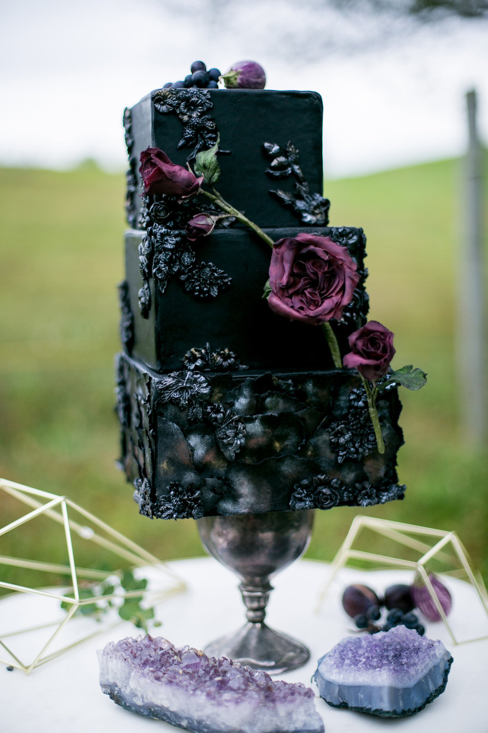 Black Wedding Cake with Purple Sugar Flowers — from Moody and Dramatic Wedding Ideas - photo by Chantal Routhier Photography — click to see more inspiration on www.BrendasWeddingBlog.com