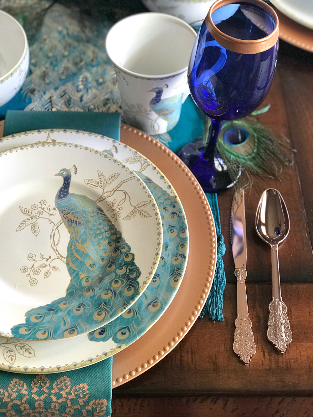 Copper, Teal and Cobalt Colored Peacock Table Setting for a peacock wedding theme (or holiday tablescape) / peacock dinnerware - the perfect choice for a wedding registry / diy gold rimmed wine glasses / as seen on Brenda's Wedding Blog www.brendasweddingblog.com / design and styling by Bri of Halfpint Design