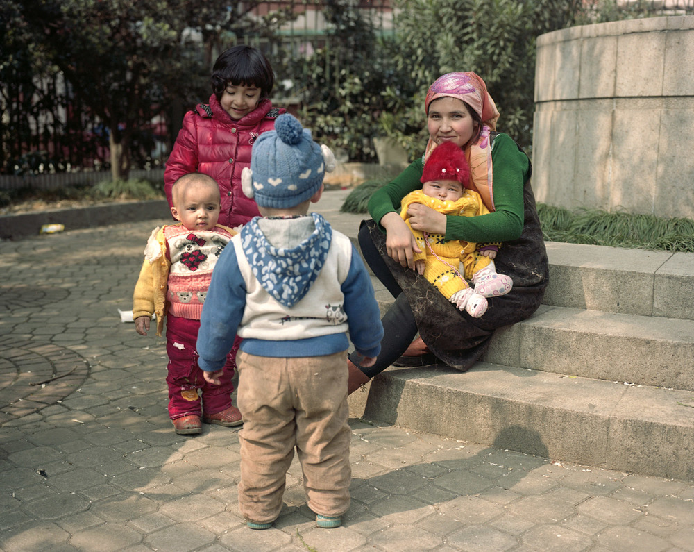 Muslim woman taking care of the kids during the friday prayer in Shanghai
