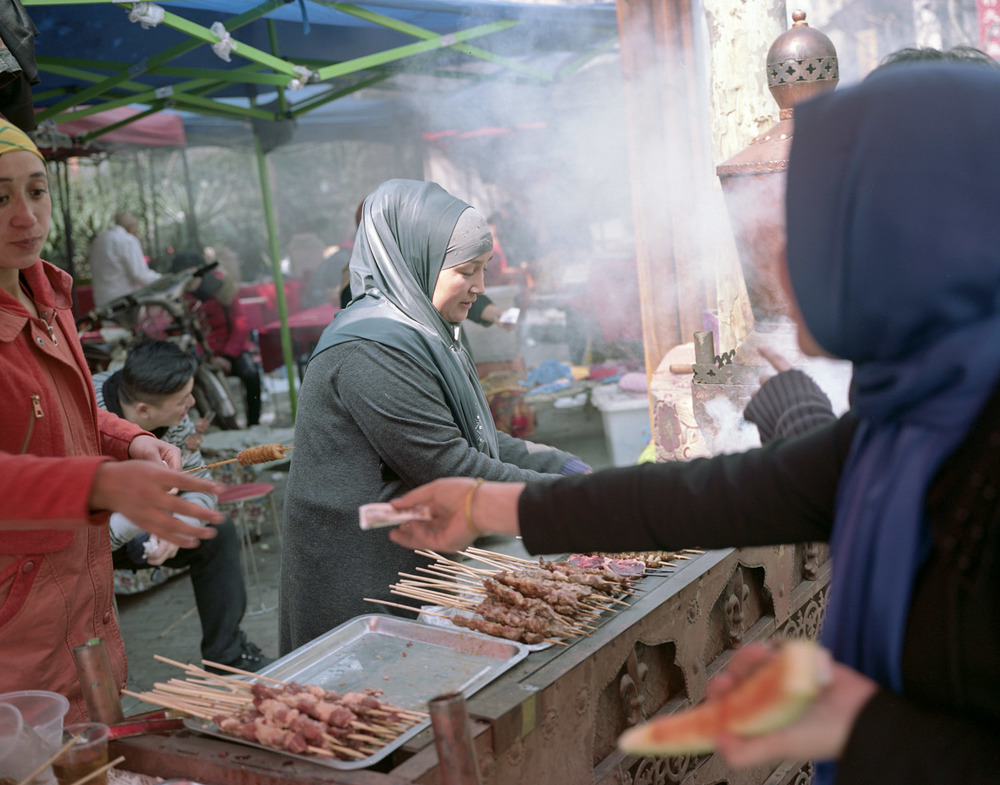 Women preparing and buying food during the men's prayer in Shanghai