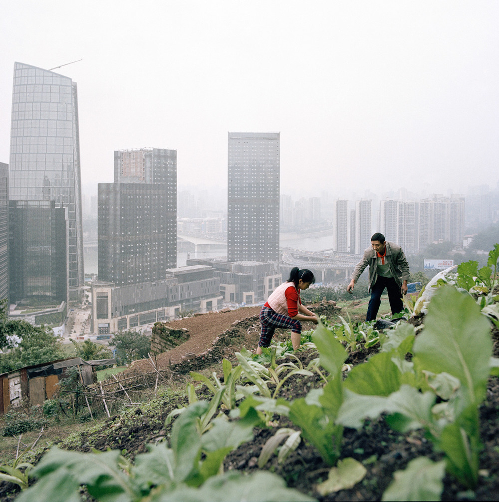 Huang Chunying and her husband work barefoot on a land above the new business developments of the Tiandi Project.