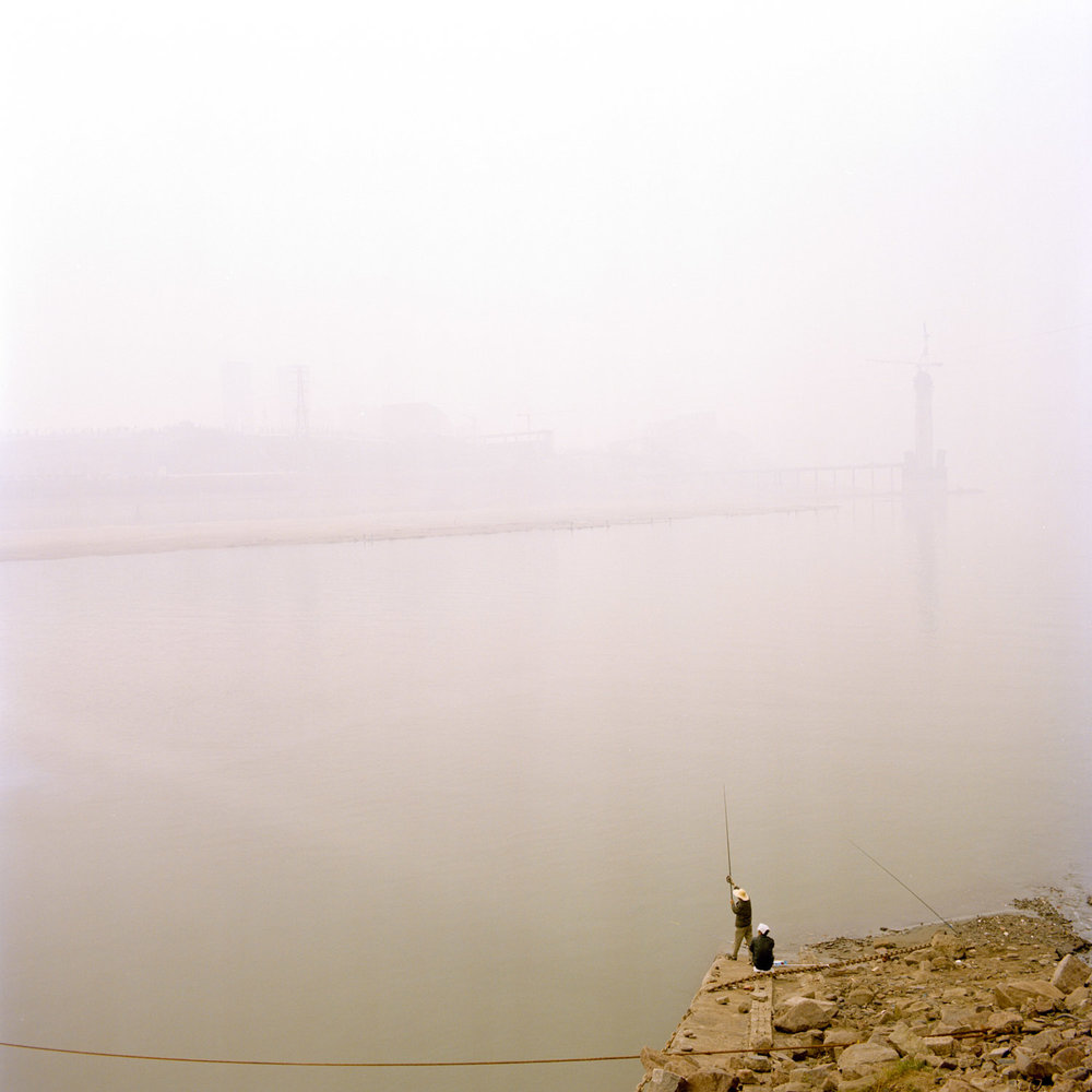 Local people fishing on the Jialing river downtown Chongqing. The polustion dust is so strong that we cant see any side of the city