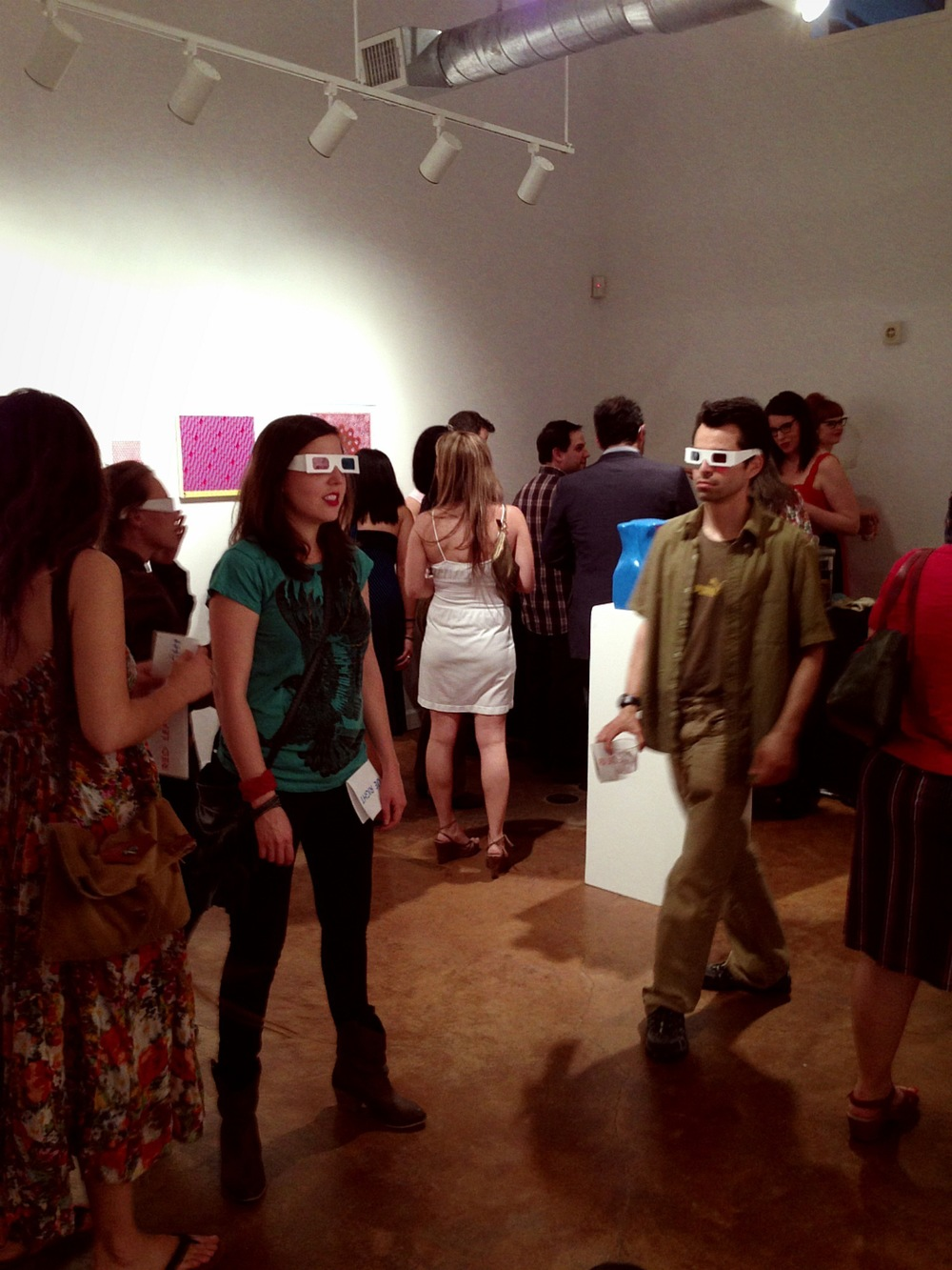 Art enthusiasts wearing 3D glasses provided by gallery.