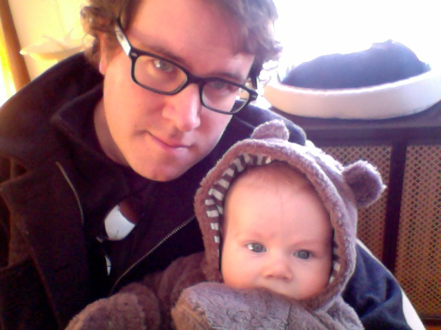 Picture of Gregory Lawless and small child with cute bear hat (presumably Gregory's son).