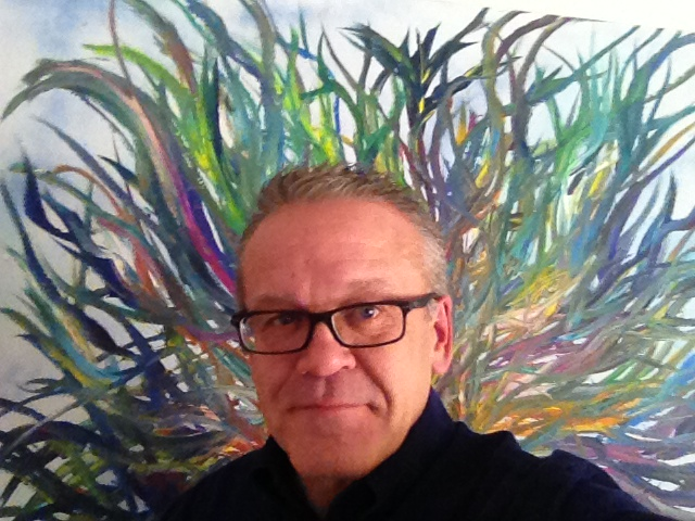 Photo of Steve Simmons in front of one of his art works of colorful green, blue and yellow/orange waves/tendrils.