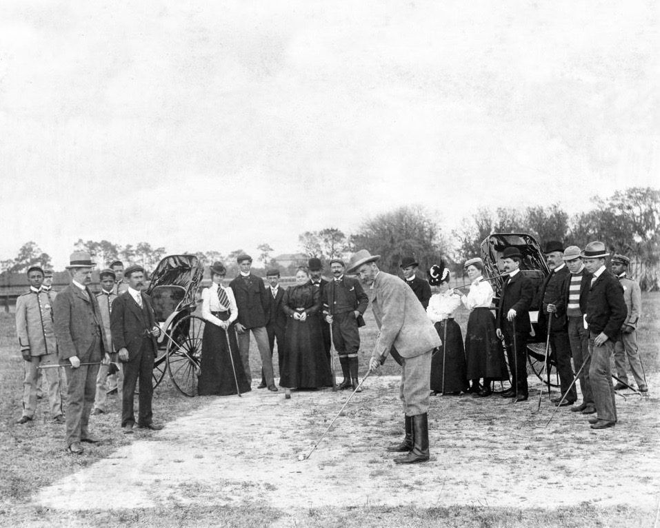 """Far left with golf club:  Morton Freeman Plant  (1852-1918), Plant System financier and railroad, steamship and hotel magnate, co-owner of the Major League Baseball National League Philadelphia Phillies, son of Plant System founder Henry Bradley Plant.   Far right with golf club:  Willie Smith  (1876-1916) of Dundee, and Carnoustie, Scotland; 1899 United States Open Champion, by 11 strokes (a record broken by Tiger Woods 101 years later). Finished Top Ten in eight of ten US Opens played, 1898-1908. Champion of inaugural Western Open if 1899. Willie's older brother Alex won the US Open in 1906 and 1910, and younger brother, PGA Hall of Fame member Macdonald was US Open runner-up in 1930 and Open Championship runner-up in 1930 and 1932.  On the tee:  Tom Dunn  (1849-1902), of Musselburgh, manager of the West Florida Golf Association. Dunn finished 6th in the 1868 Open Championship as an amateur; and top ten four of eight appearances; turned professional in 1869 as green-keeper and club-maker at North Berwick and in 1870 moved to London Scottish Golf Club, Wimbledon; and in 1889 to Biarritz, France. In 1894, won the Championship of America at St. Andrews Golf Club, Yonkers, New York. Claimed to have laid out 137 golf courses.  Son of Willie Dunn, who competed in the 2nd Open Championship in 1861, finishing 7th.  Brother of Willie Dunn, Jr., 1895 finished US Open runner-up, professional at Westward Ho!, Biarritz, Newport Country Club and Ardsley Country Club; designer of Shinnecock Hills Golf Club, Maidstone Club and and Apawamis Club; club maker and designer, inventing the aluminum-clad """"indestructible driver and developed praline use in woods and putters.  Tom Dunn's two sons were also noted golf professionals and course designers, in the Netherlands."""