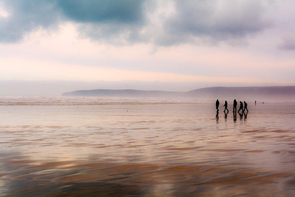 Group of people walking on a sandy beach in wet weather