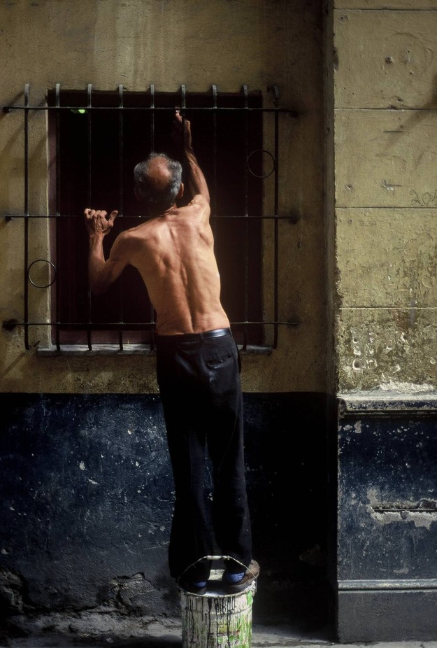 man repairing window old havana cuba