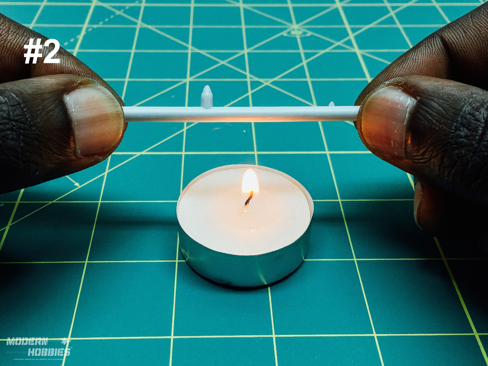 I hold the sprue over a candle flame and slowly rotate it to soften the plastic.  Be careful not to hold the plastic directly in the flame to avoid it catching fire.