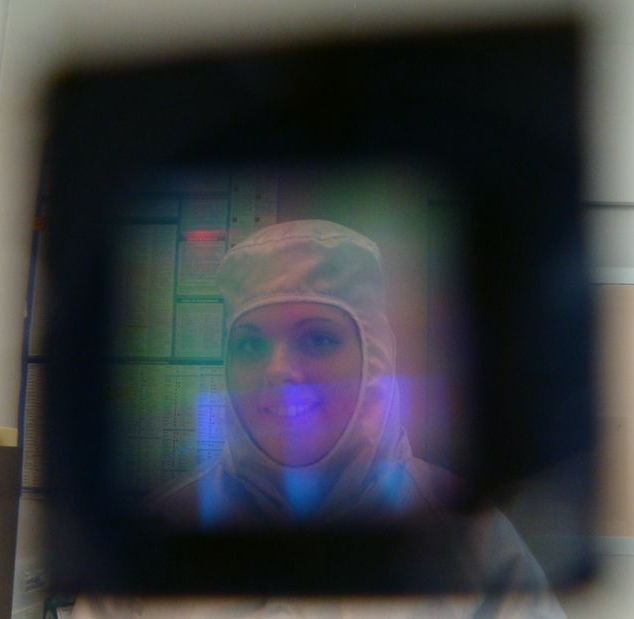 This is a picture taken through a 500nm pitch nanohole array imprinted on aluminum with the hole diameters = 150nm. Theoretically, the film should be opaque and not allow wavelengths larger than the hole diameter to penetrate, but coupling between incident light and surface plasmons promotes light penetration. Thus the film appears much more transparent and you can see Alyssa through the grating.