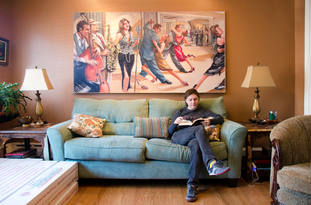Tim Johnson unwinds from work by reading a book at his home in South Philadelphia on March 9, 2014.