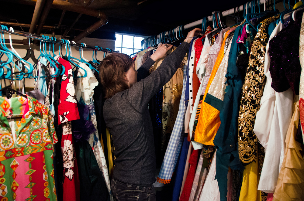 Johnson searches through racks of vintage and repurposed dresses in the basement of his home as he looks for an outfit to wear to a gig on March 9, 2014.